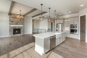 Holzfliesen im Wohnbereich und Küche sowie Kamin aus Natursteinkacheln